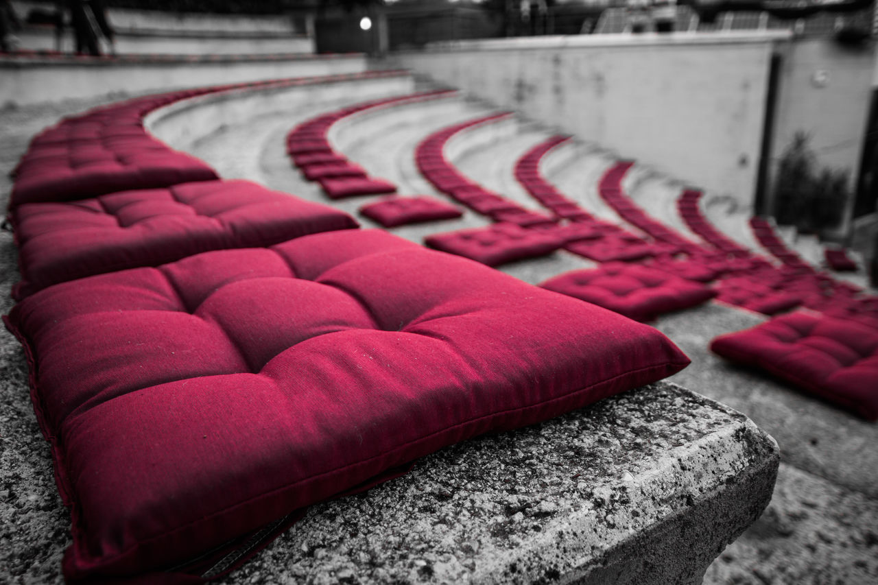 seat, no people, in a row, red, absence, focus on foreground, empty, day, chair, arrangement, outdoors, large group of objects, carpet - decor, repetition, close-up, furniture, sport, side by side, order, architecture, concrete