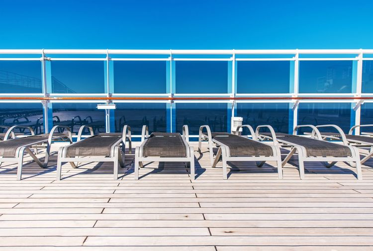 Cruise Ship Sea Travel Concept with Wooden Deckchairs on the Open Deck of the Ship. Cruise Ship Blue Clear Sky Day Deck Deckchair In A Row Nature No People Outdoors Railing Sea Sea Travel Sea Traveling Sky Sunlight Swimming Pool Transportation Water