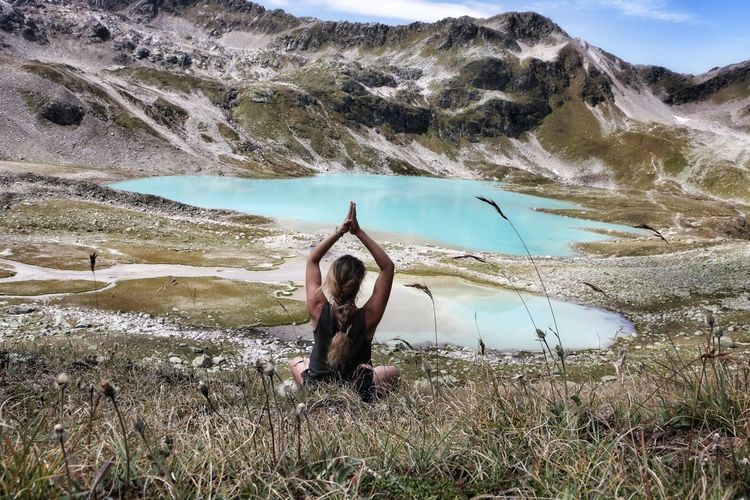 Rear view of woman doing yoga against mountain