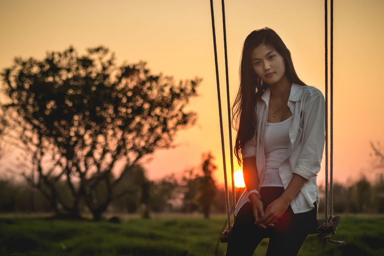 Beautiful young woman sitting on swing against sky during sunset