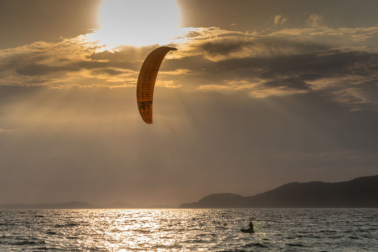 Man kiteboarding in sea against sky during sunset