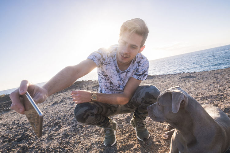 Full Length Of Man Taking Selfie With Dog While Crouching On Sand At Beach Against Sky