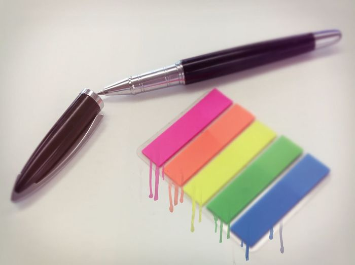 Close-up of pen with various colors on white background