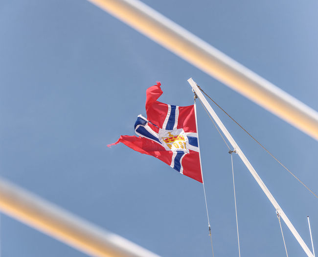 Low angle view of flag waving against clear blue sky