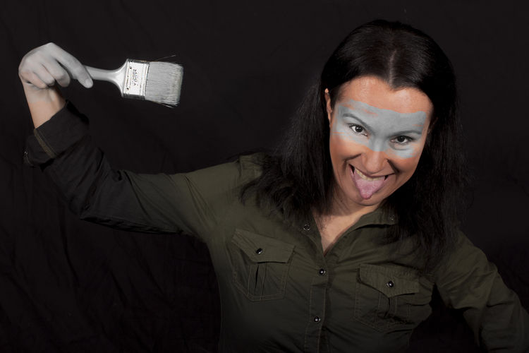 Portrait of woman sticking out tongue while holding paintbrush against black background