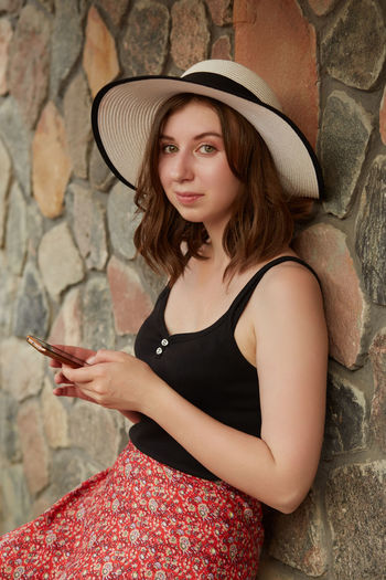 Portrait of beautiful young woman using mobile phone against wall