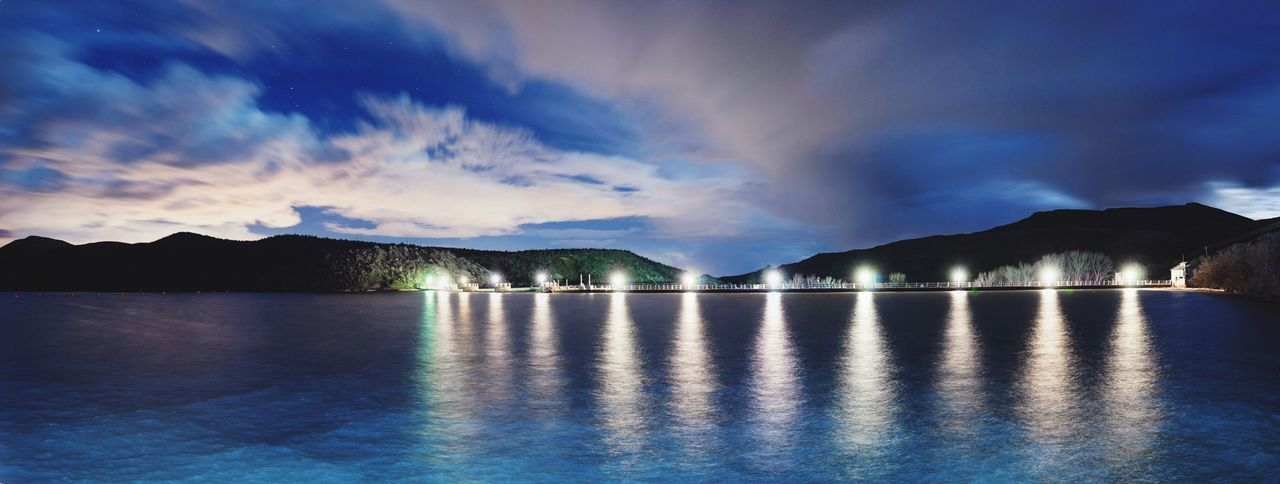 Panoramic shot of reservoir against cloudy sky at night