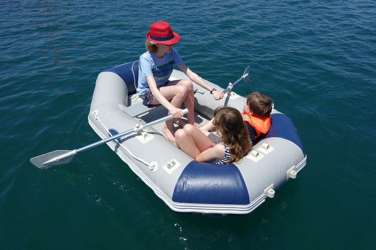 Three children having fun in an inflatable dinghy