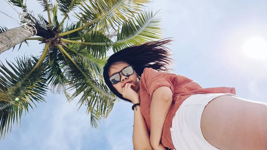Low angle view of young woman on palm tree against sky