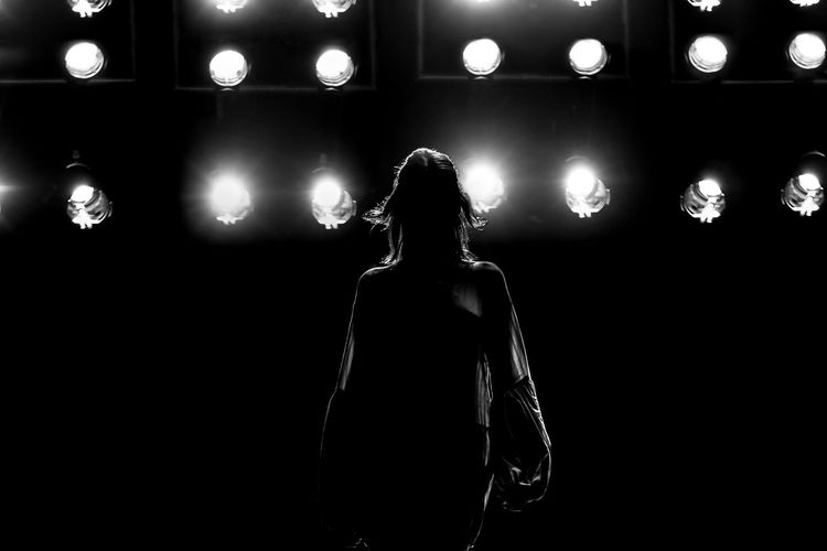 Rear view of woman standing against illuminated lights at night