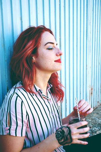 Beverage Adult Beautiful Woman Beauty Casual Clothing Contemplation Drink Drinking Glass Dyed Hair Hair Hairstyle Holding Iron Leisure Activity Lifestyles Looking Looking Away One Person Portrait Real People Redhead Striped Women Young Adult Young Women