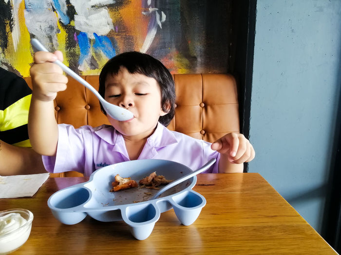 Table Real People Childhood Child Food And Drink Indoors  One Person Front View Food Sitting Lifestyles Leisure Activity Holding Innocence Casual Clothing Kitchen Utensil Eating Utensil Home Interior
