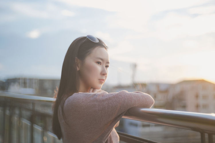 Side view of young woman looking away against sky