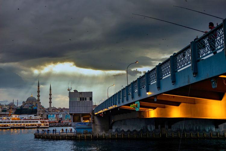 Bridge over river against sky at dusk