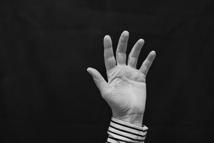 Cropped image of person hand against black background