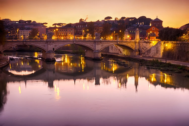 Old arch bridge over tiber river in illuminated town against sky during sunset