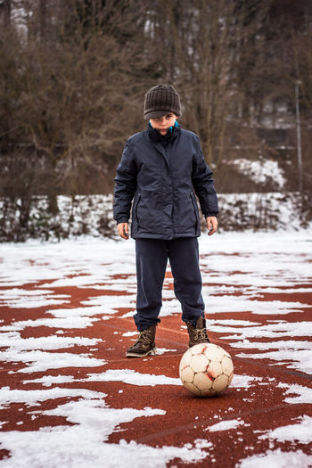 Full Length Of Boy Playing Soccer During Winter