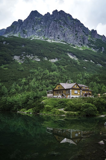 Houses by lake and mountains against sky