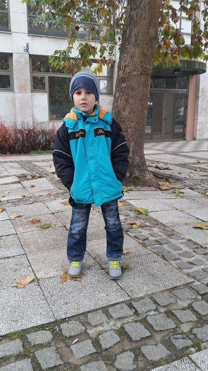 Full length portrait of boy standing on footpath
