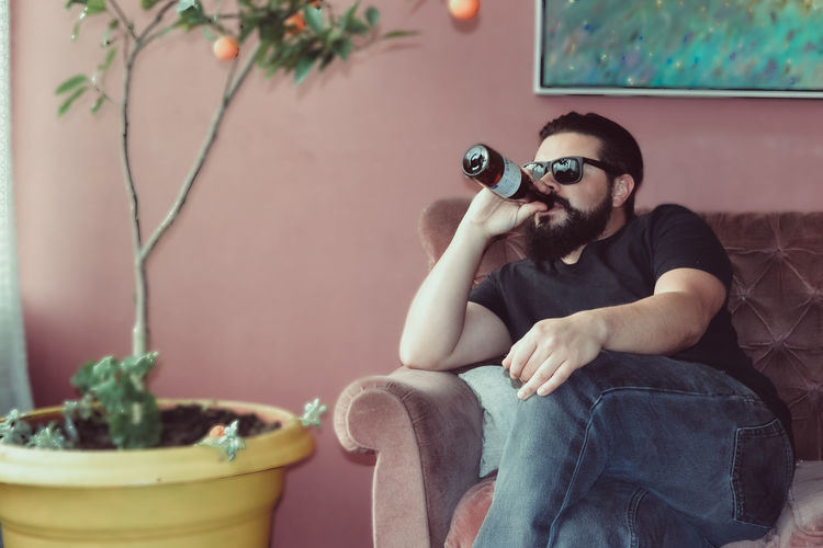 Man drinking beer while sitting on sofa