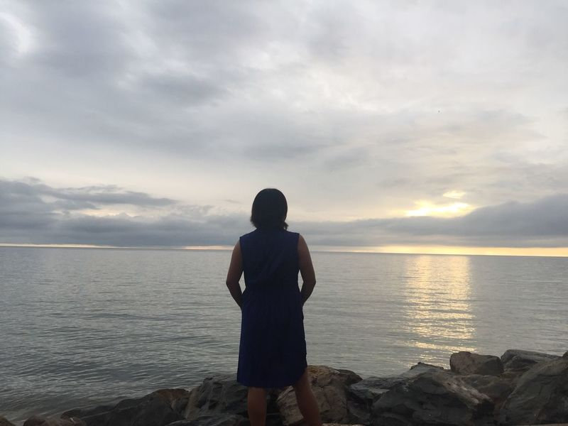 rear view of woman standing at sea shore against sky Beach Beauty In Nature Cloud - Sky Day Horizon Over Water Lifestyles Nature One Person Outdoors People Photograhy Real People Rear View Scenics Sea Sky Standing Sunset Tranquil Scene Tranquility Water