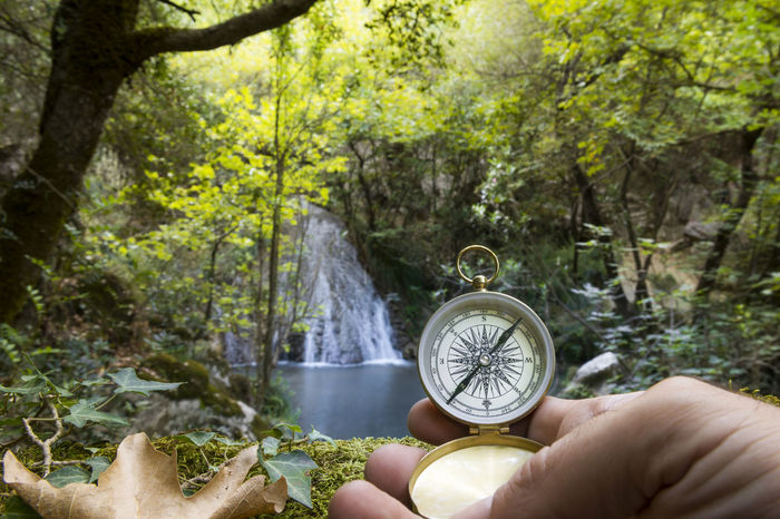 Man's hand holding a compass in the forest, concept of seeking, exploration, achievement. Achievement Adult Adventure Compass Decision Discovery Exploration Forest Green Nature Guide Hiking Holding Human Hand Lake Lost Nature Pool River Searching Seeking Trail Treasure Hunting Trees Trekking Waterfall