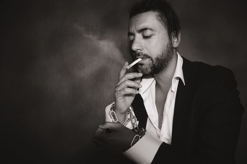 Young Gangster Smoking Cigarette Against Wall