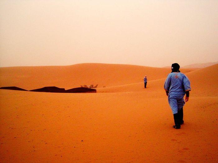 Man Standing On Sand Dune In Desert