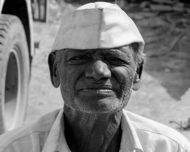 Close-up portrait of senior man wearing cap