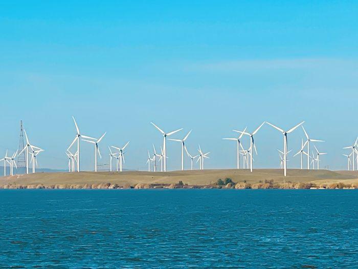 Wind turbines by sea against blue sky