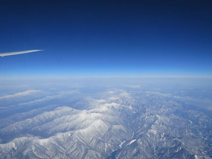 Aerial view of snowcapped mountains against clear blue sky