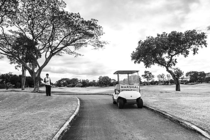 Golf Marshal in a beautiful scenery. Bare Tree Beauty In Nature Black And White Caddie Cloud Cloud - Sky Day Golf Grass Growth Landscape Marshal Nature Outdoors Road Scenics Sky The Way Forward Tranquil Scene Tranquility Tree