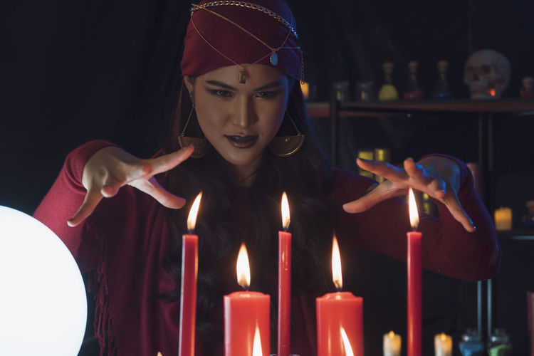 Female fortune teller with burning candles at home