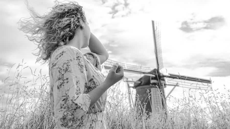 Low angel view of woman standing by windmill in farm