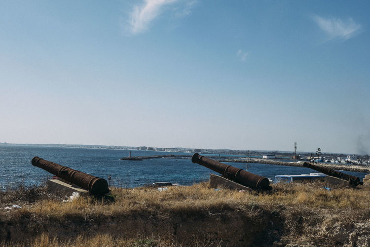 Scenic view of sea against sky with canons