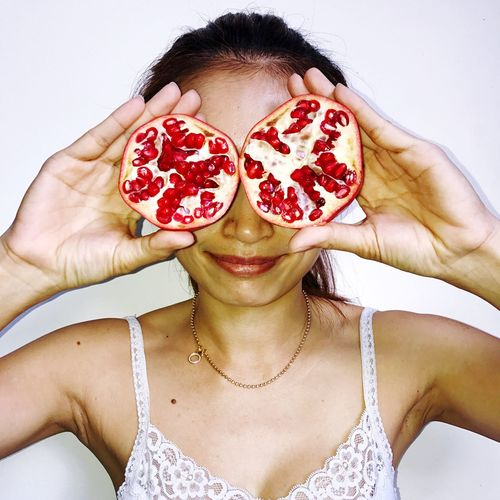 Smiling woman holding halved pomegranate against white background
