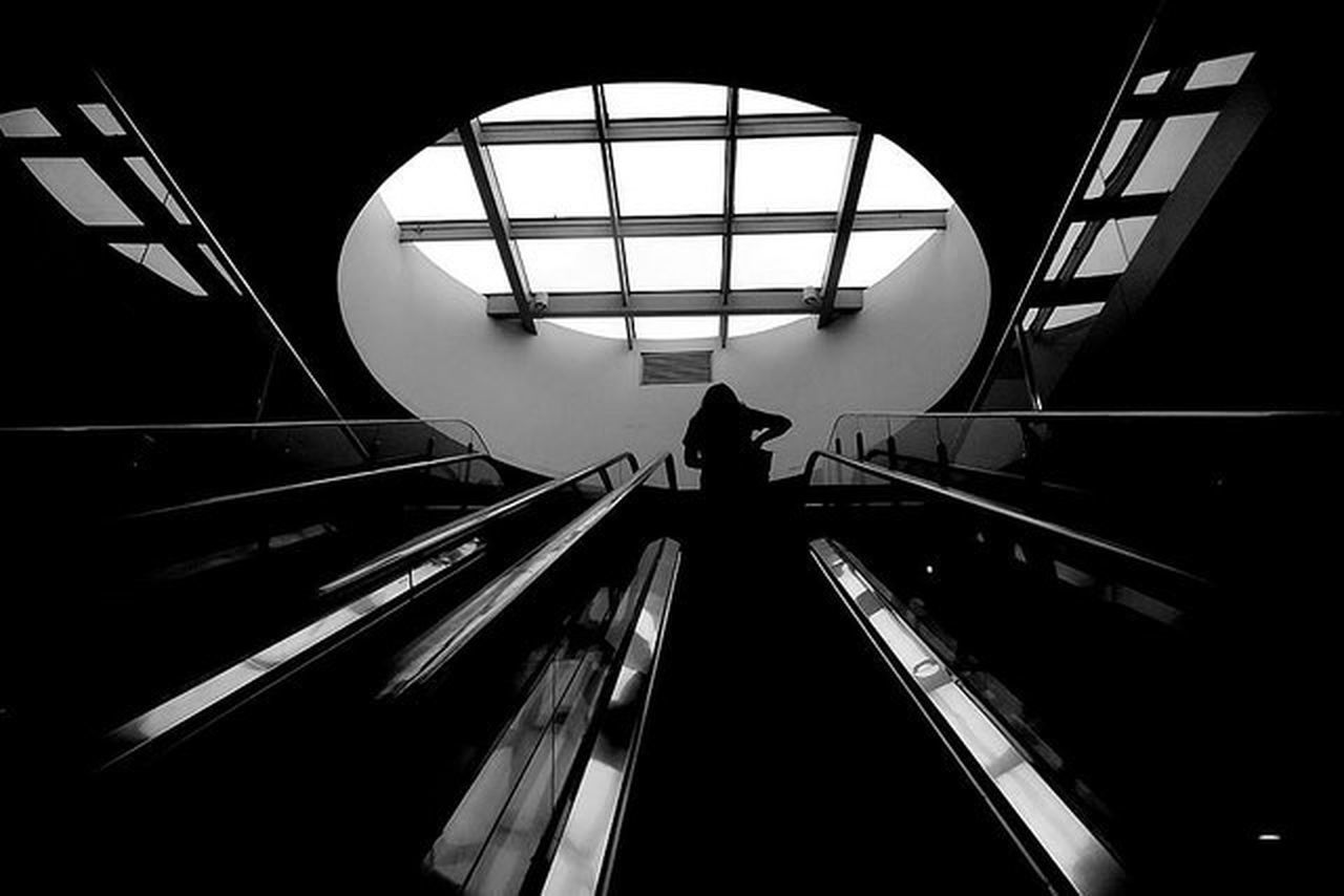 Low angle view of silhouette woman on escalator