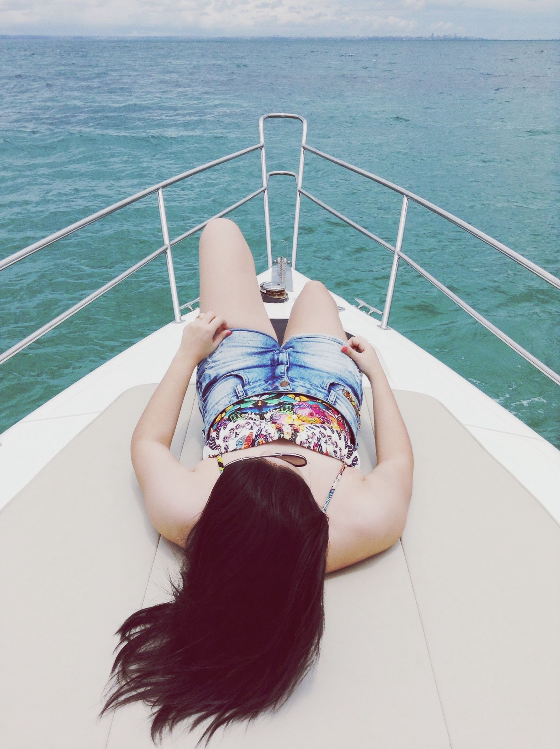 water, leisure activity, lifestyles, sea, vacations, sitting, person, relaxation, high angle view, sunlight, young adult, young women, summer, day, enjoyment, boat, outdoors, full length