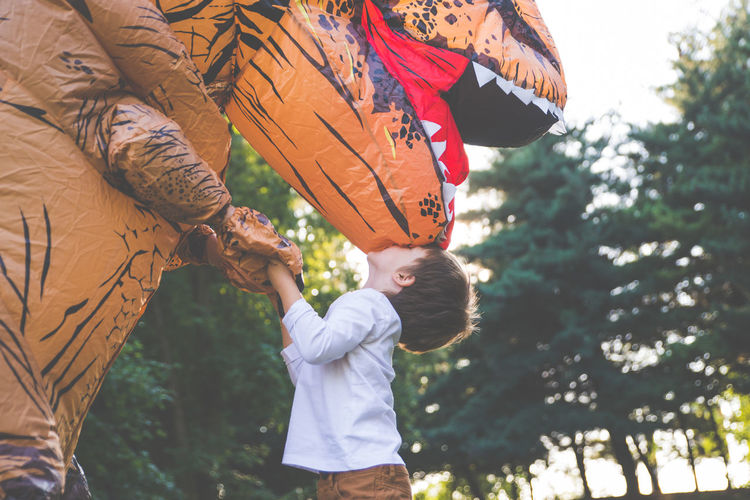 Boy kissing person wearing dinosaur costume in park