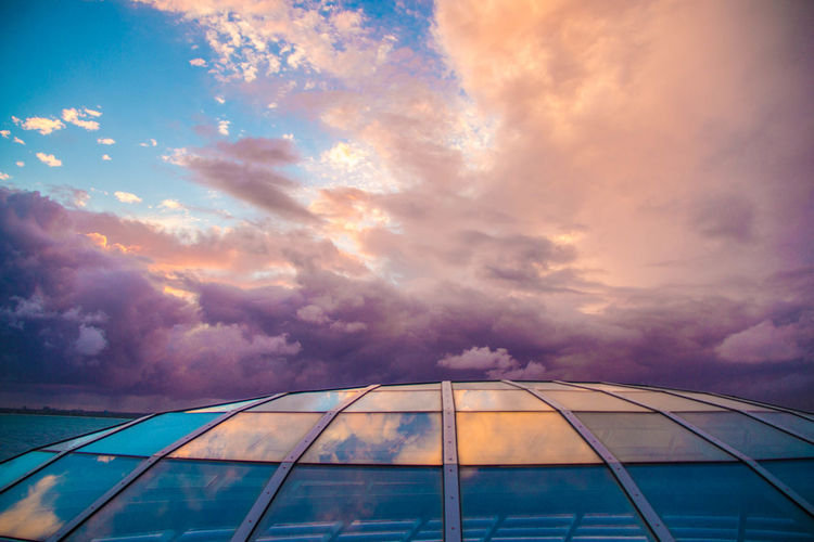 Low angle view of glass building against sky during sunset