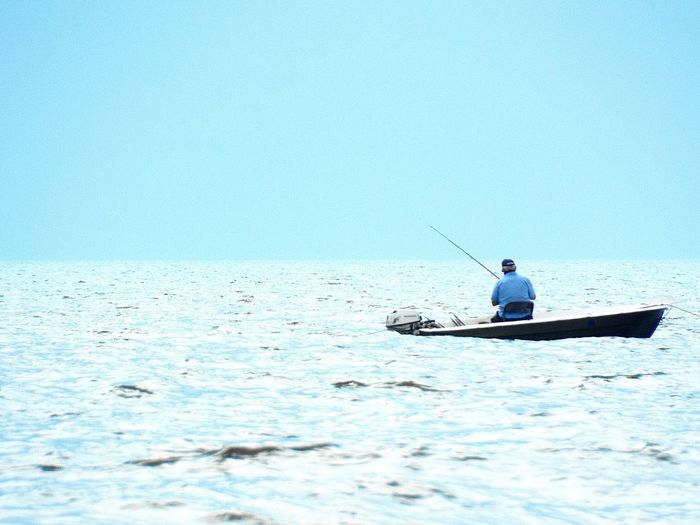 Man In Fishing Boat Against Clear Sky