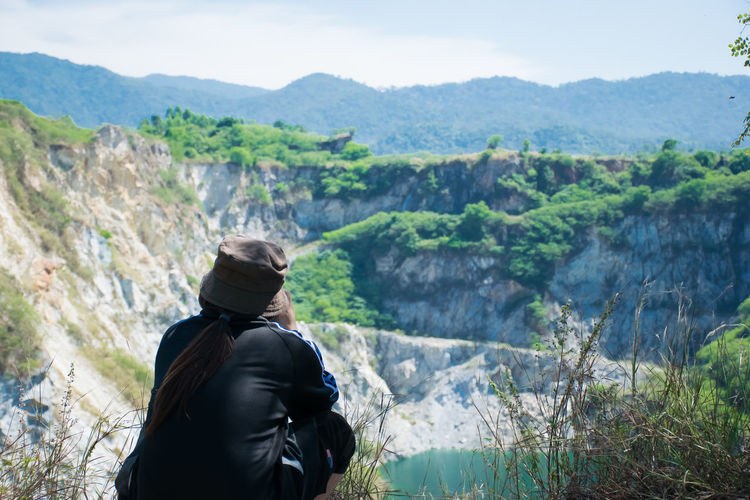 Rear view of man crouching while looking at mountains