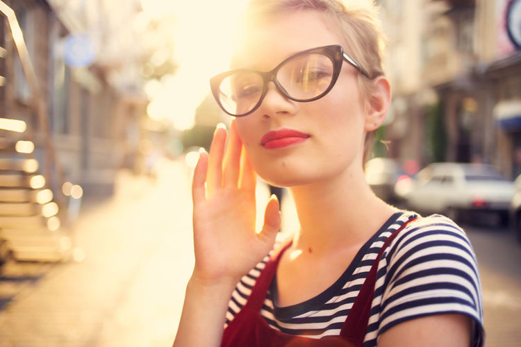 Portrait of young woman holding eyeglasses