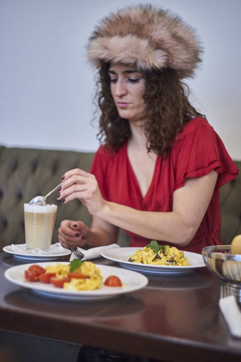 Mature Woman Sitting With Food On Table At Restaurant