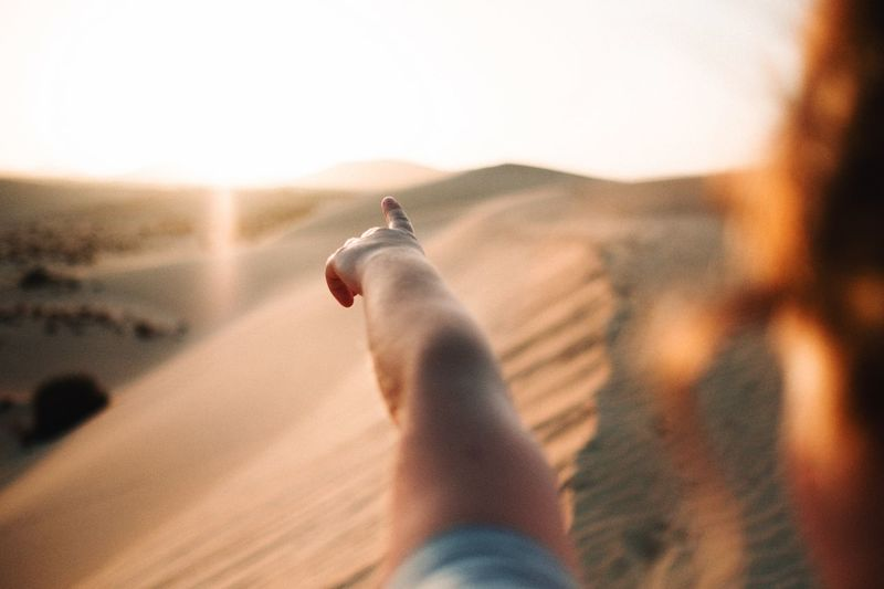 Close-up of woman pointing in desert during sunset