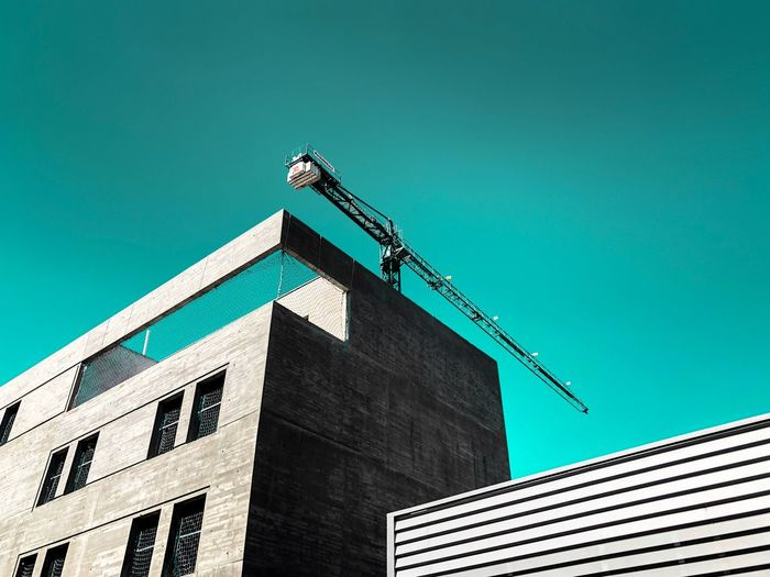 Low angle view of crane on building against clear blue sky