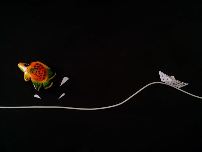 Artificial fish with paper boat and cable against black background