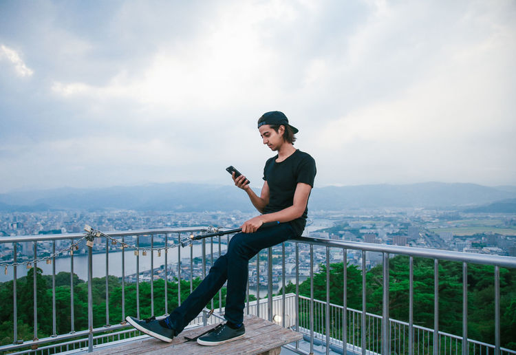 Full length of man using phone while sitting on railing against cityscape