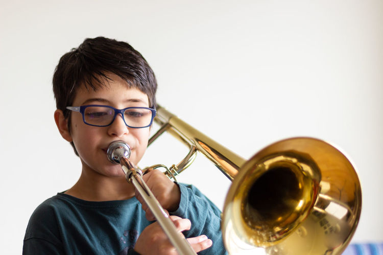 Boy playing trombone against wall