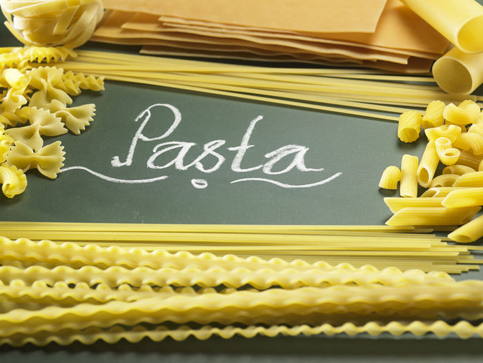 Close-up of raw pastas and text on black background